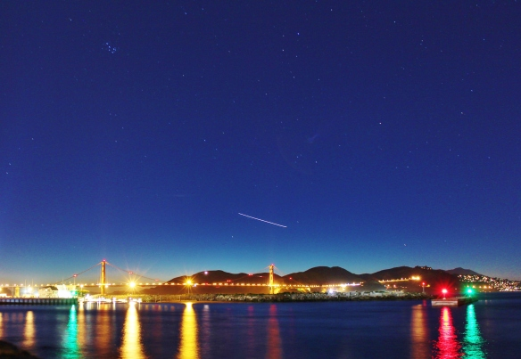 The Golden Gate Bridge at night, with planes and stars overhead